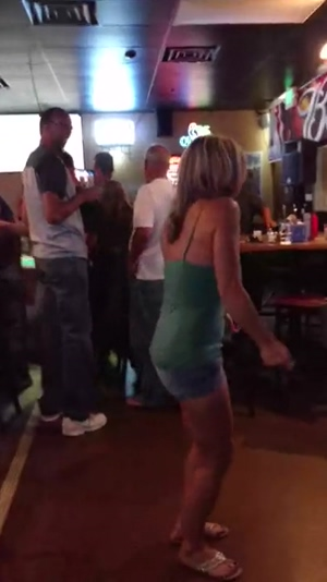 In the bar, a mature blonde dances and shows boobs