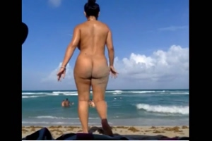 Brunette with big tits and big ass bathes naked on a sandy beach
