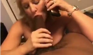 Mature lady sucking a big black monster cock while on the phone